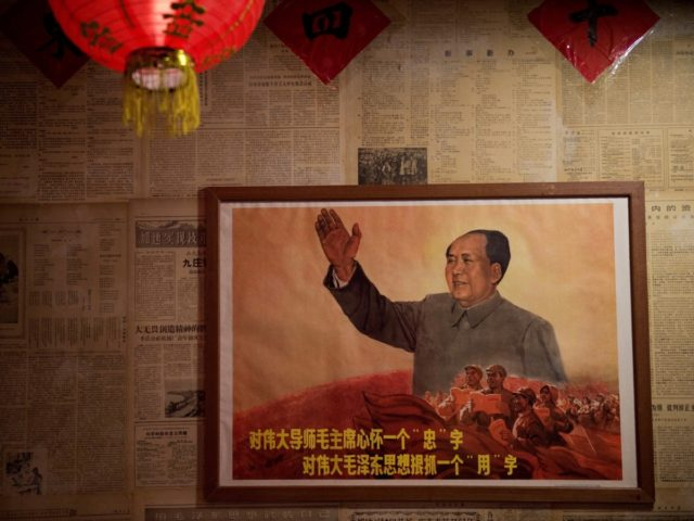 A poster showing the late Chinese chairman Mao Zedong hangs on a wall inside a restaurant in Beijing on May 13, 2016. Fifty years after the Cultural Revolution spread bloodshed and turmoil across China, the Communist-ruled country is driving firmly down the capitalist road, but Mao Zedong's legacy remains -- …
