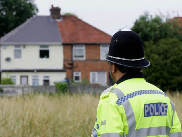 Birmingham, UNITED KINGDOM: A policeman stands guard 27 July 2005 at the back of a house on Heybarnes Rd in Birmingham after a man was arrested there in connection with the 21 July 2005 bombing attempts made on London's transport system. AFP PHOTO / CARL DE SOUZA. (Photo credit should …