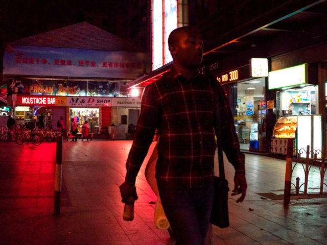 """In this photo taken on March 1, 2018, people walk in the """"Little Africa"""" district in Guangzhou, the capital of southern China's Guangdong province. - The commercial hub has long been a magnet for fortune-seeking Africans, but traders and students say they face unfavourable visa rules and increasingly heavy policing. …"""
