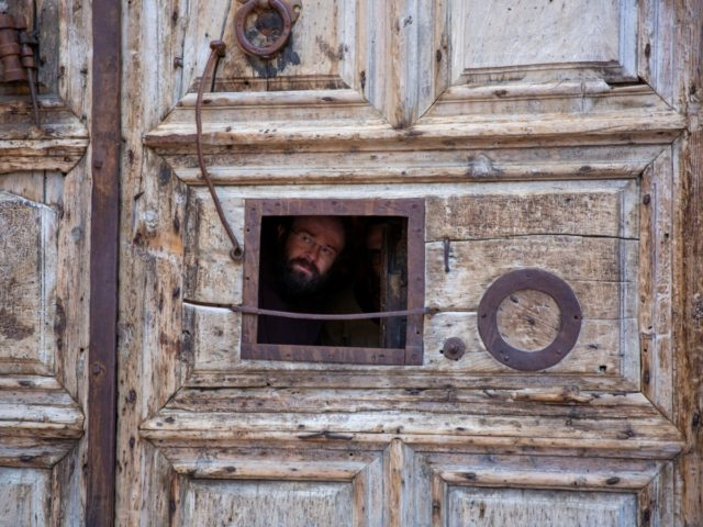 A priest peers from a window in the door of the Church of the Holy Sepulchre, a place where Christians believe Jesus Christ was buried, just before Archbishop Pierbattista Pizzaballa arrives during a lockdown following government measures to help stop the spread of the new coronavirus, during Holy Thursday in …