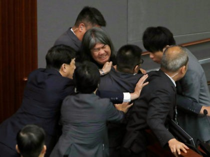 "Newly elected pro-democracy lawmaker Leung Kwok-hung, known as ""Long Hair,"" top center, tries to break through the security guards during the election of president of the Legislative Council in Hong Kong, Wednesday, Oct. 12, 2016. A swearing-in ceremony to kick off Hong Kong's legislative session descended into farce Wednesday as …"