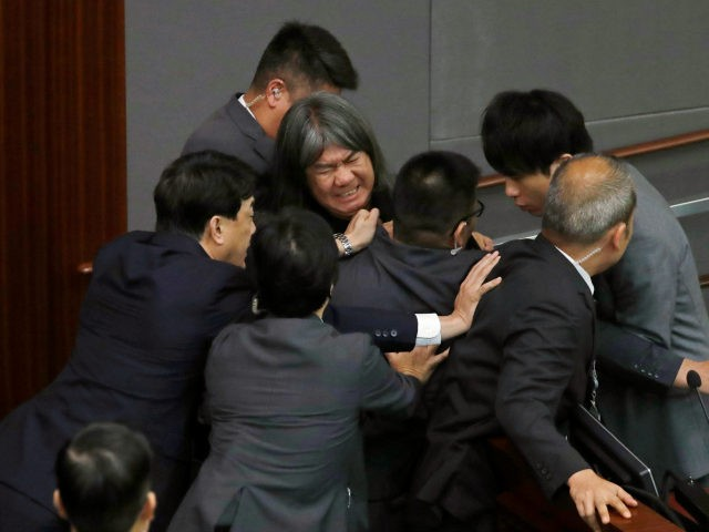 """Newly elected pro-democracy lawmaker Leung Kwok-hung, known as """"Long Hair,"""" top center, tries to break through the security guards during the election of president of the Legislative Council in Hong Kong, Wednesday, Oct. 12, 2016. A swearing-in ceremony to kick off Hong Kong's legislative session descended into farce Wednesday as …"""