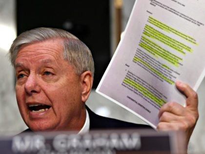 "Senate Judiciary Committee Chairman Lindsey Graham, R-S.C., holds up a copy of the ""Steele Dossier"" during a hearing with Department of Justice Inspector General Michael Horowitz on Capitol Hill in Washington, Wednesday, Dec. 11, 2019, to look at the Inspector General's report on alleged abuses of the Foreign Intelligence Surveillance …"