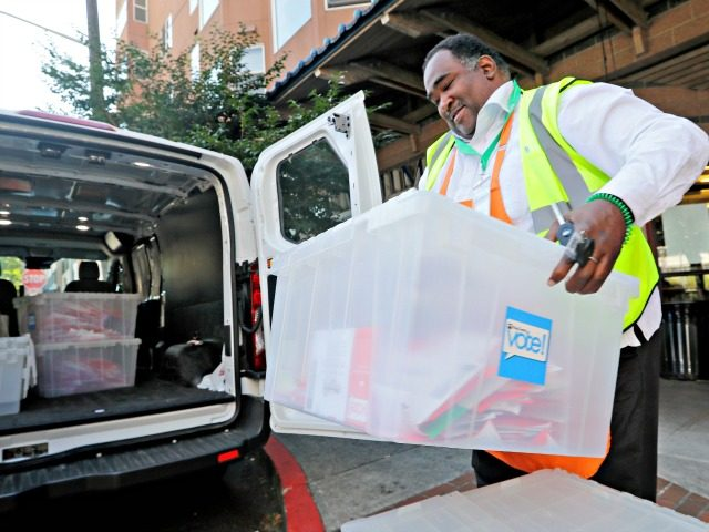 In this Aug. 7, 2018 file photo, King County Election official Joseph Emanuel loads ballots into a van after collecting them from a drop box in Seattle. If control of the U.S. House comes down to any of the competitive congressional races in Washington state and California, the American public …