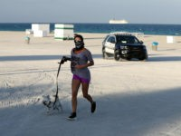 A jogger and her dog are turned away from a closed beach by a police officer, Wednesday, March 25, 2020, in Miami Beach, Fla.'s famed South Beach. (AP Photo/Wilfredo Lee)