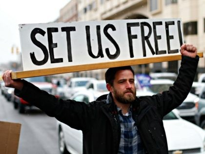 Steve Polet holds a sign during a protest at the State Capitol in Lansing, Mich., Wednesday, April 15, 2020. Flag-waving, honking protesters drove past the Michigan Capitol on Wednesday to show their displeasure with Michigan Gov. Gretchen Whitmer's orders to keep people at home and businesses locked during the new …