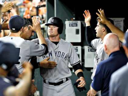 New York Yankees' Clint Frazier, center, high-fives teammates in the dugout after scoring during the ninth inning against the Baltimore Orioles in a baseball game Wednesday, July 11, 2018, in Baltimore. New York won 9-0. (AP Photo | Patrick Semansky)AP