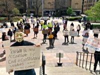 About 75 people wearing masks and carrying signs protest outside the Ohio Statehouse on Thursday, April 9, 2020, in Columbus, Ohio. The protesters criticized the state's shutdown of the economy, called on Ohio Gov. Mike DeWine to re-open businesses, and questioned the models used by Health Director Dr. Amy Acton …