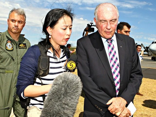 PERTH, AUSTRALIA - MARCH 22: Acting Australian Prime Minister Warren Truss talks with a Chinese reporter from Phoenix TV after addressing local and international media about the search for possible Malaysian Airlines flight MH370 debris off the coast of Western Australia at RAAF Base Pearce on March 22, 2014 in …
