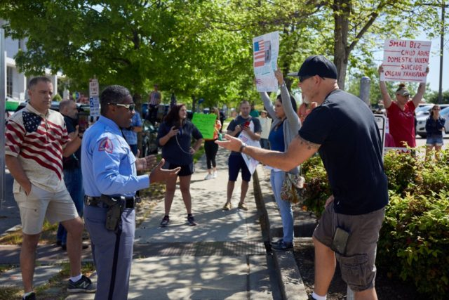 Protesters from a grassroots organization called REOPEN NC argue with a Raleigh police officer during a demonstration against the North Carolina coronavirus lockdown at a parking lot adjacent to the North Carolina State Legislature in Raleigh, North Carolina, on April 14, 2020. - The group was demanding the state economy …