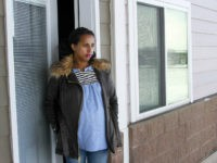 In this April 13, 2020, photo, Kulule Amosa steps out of the apartment she shares with her husband who works at the Smithfield Foods pork processing plant in Sioux Falls, S.D. He tested positive for the coronavirus this week after an outbreak at the plant. (AP Photo/Stephen Groves)