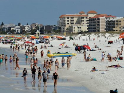 Visitors enjoy Clearwater Beach, Wednesday, March 18, 2020, in Clearwater Beach, Fla. Beach goers are keeping a safe distance from each other to help protect from the spread of the Coronavirus. (AP Photo/Chris O'Meara)