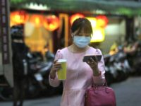 aptopix-virus-outbreak-taiwan-woman-protective-mask-balances-sized-cup-watching-smart-pho-640x448