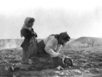 """An Armenian woman kneeling beside a dead child in a field """"within sight of help and safety at Aleppo"""". Source: Wikipedia"""