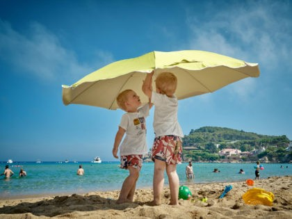 Beachgoers, little boys with beach umbrella