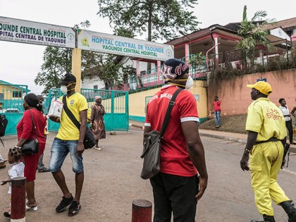 Some people wear masks as they walk by the entrance to the Yaounde General Hospital in Yaounde on March 6, 2020 as Cameroon has confirmed its first case of the COVID-19 coronavirus, a French national who arrived in the capital Yaounde in February, the government said on today. - The …