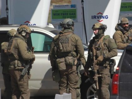 Members of the Royal Canadian Mounted Police (RCMP) tactical unit confer after the suspect in a deadly shooting rampage was neutralized at the Big Stop near Elmsdale, Nova Scotia, Canada, on April 19, 2020. - A gunman killed at least 10 people in an overnight shooting rampage across rural Nova …