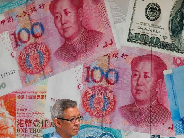 FILE - In this Aug. 6, 2019, file photo, a man walks by a money exchange shop decorated with Chinese yuan banknotes and other countries currency banknotes at Central, a business district in Hong Kong. China allowed its yuan to sink to an 11-year low against the dollar after U.S. …