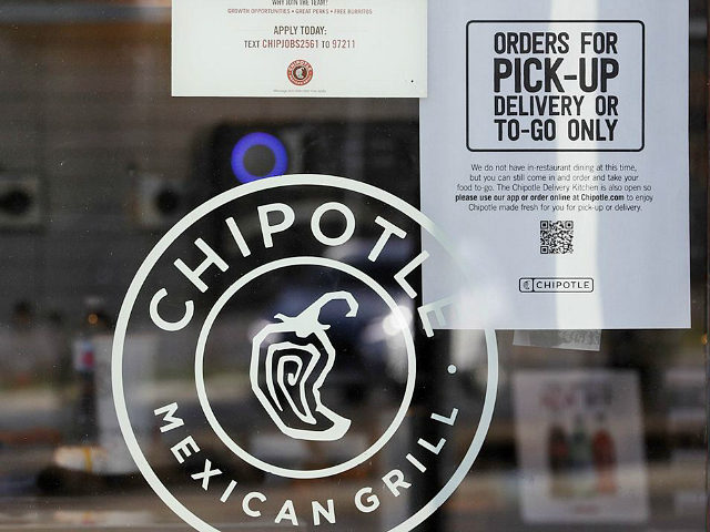"""A sign hangs in the window at Chipotle Mexican Grill, Monday, March 16, 2020, in Woodmere Village, Ohio. All bars and restaurants in Ohio will be closed until further notice, said Gov. Mike DeWine, who is taking a tough stance on trying to stem the coronavirus saying """"if we don't …"""