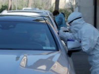 Medical staff of a mobile unit take samples from people in cars to test for Covid-19 at a drive-through position at the Santa Maria della Pieta' hospital complex, in Rome, Friday, April 3, 2020. The new coronavirus causes mild or moderate symptoms for most people, but for some, especially older …