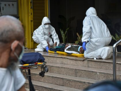 Paramedics wearing protective suits amid fears of coronavirus outbreak check on a man who collapsed outside a clinic in Jakarta, Indonesia, Thursday, March 26, 2020. It's not immediately clear what caused the man to collapse. The U.S. Embassy in Indonesia has ordered the departure of employees' family members under the …