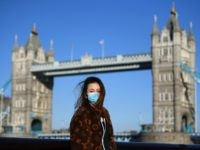 LONDON, ENGLAND - MARCH 22: A member of the public poses for a photo in front of Tower Bridge whilst wearing a protective mask on March 22, 2020 in London, England. Coronavirus (COVID-19) has spread to at least 188 countries, claiming over 13,000 lives and infecting more than 300,000 people. …