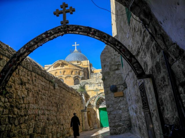 A monk walks near the Church of the Holy Sepulchre before the start of the Easter Sunday service amid the coronavirus disease (COVID-19) outbreak, in Jerusalem's Old City on April 12, 2020. - All cultural sites in the Holy Land are shuttered, regardless of their religious affiliation, as authorities seek …