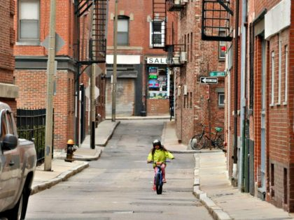 A young girl rides her bike on Boston streets now empty due to the coronavirus disease COVID-19. Joseph Prezioso / AFP Getty Images