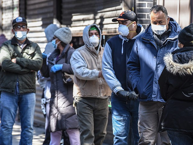 NEW YORK, NY - APRIL 1: People stand in line while wearing face masks in the Elmhurst neighborhood on April 1, 2020 in New York City. With more than 75,000 confirmed cases of COVID-19 and more than 1,000 deaths, New York City has become the epicenter of the outbreak in …
