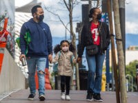A family walks wearing masks in Downtown Los Angeles on March 22, 2020, during the coronavirus (COVID-19) outbreak. - The US president on March 22 said he had ordered the deployment of emergency medical stations with capacity of 4,000 hospital beds to coronavirus hotspots around the United States. (Photo by …
