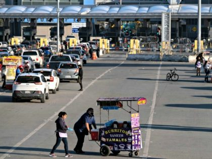 Street vendors wear face masks as a preventive measure to avoid the spread of COVID-19 at the San Ysidro crossing in Tijuana on April 23, 2020. (Credit: Guillermo Arias / AFP / Getty Images)