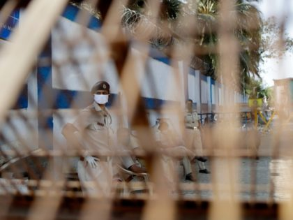 Police officers keep guard near a barricade after the locality was sealed following cases of COVID-19 in the area, in Worli village, Mumbai, India, Tuesday, March 31, 2020. India is adding more resources to tackle its increase in coronavirus cases by announcing that private hospitals may be requisitioned to help …