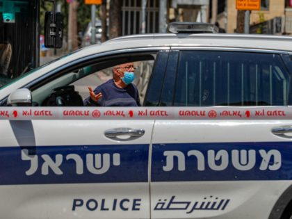 An Israeli man gestures from behind a police car, stationed at the entrance of the Mea Shearim neighbourhood in Jerusalem on April 12, 2020, during the novel coronavirus pandemic crisis. (Photo by AHMAD GHARABLI / AFP) (Photo by AHMAD GHARABLI/AFP via Getty Images)