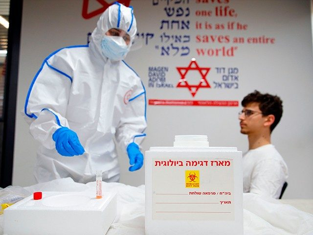 Israeli Paramedics of Maguen David Adom (Israel's National Emergency Pre-Hospital Medical Organisation) at the coronavirus national operations center, perform a coronavirus test exercise on a volunteer on February 26, 2020 in the central Israeli city of Kiryat Ono. - Some 80,000 people are infected worldwide, including nearly 2,800 outside China, …