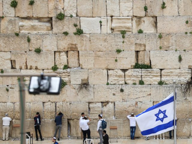 People pray at the nearly deserted Western Wall, Judaism's holiest prayer site, after Israel has imposed some of the world's tightest restrictions to contain COVID-19 coronavirus disease, in Jerusalem on March 12, 2020. - Israel imposed a two-week quarantine on all travellers entering the country, almost stopping tourism and limiting …