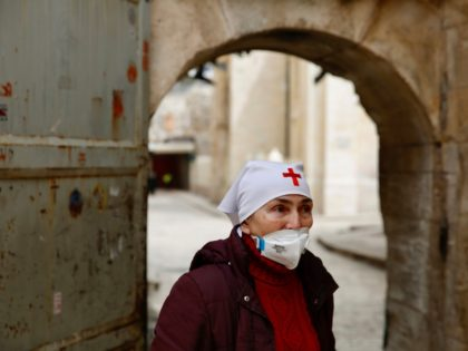 A nun wears a mask to help prevent the spread of the coronavirus next to the closed Church of the Holy Sepulchre, a place where Christians believe Jesus Christ was buried as a palm hangs on the door in Jerusalem's old city, Sunday, April 5, 2020. The traditional Palm Sunday …