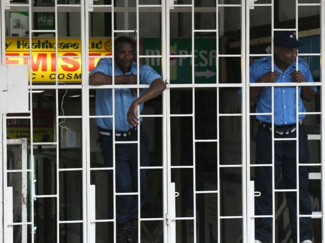 Private security guards watching behind the grills before the beginning of a curfew which was ordered by the Kenyan President, Uhuru Kenyatta, to contain the spread of the COVID-19 coronavirus on March 27, 2020 in Nairobi. - Kenyan President Uhuru Kenyatta on March 25, 2020, ordered a nighttime curfew to …