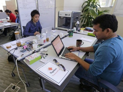 In this Thursday, June 30, 2016 photo, Babson College graduate school alumnus Abhinav Sureka, of Mumbai, India, right, types in his work space at the college in Wellesley, Mass. Some U.S. colleges are starting programs to help their alumni get visas through what critics say is a legal loophole. Foreign …