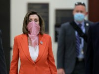 WASHINGTON, DC - APRIL 24: Wearing a scarf over her mouth and nose, Speaker of the House Nancy Pelosi (D-CA) is surrounded by security and staff as she arrives for her weekly news conference during the novel coronavirus pandemic at the U.S. Capitol April 24, 2020 in Washington, DC. President …