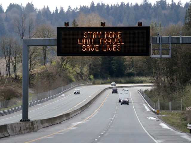 """A sign overhead on an unusually quiet highway reminds drivers to """"Stay home, limit travel, save lives"""" as part of Gov. Jay Inslee's ongoing stay-at-home order in the midst of the coronavirus outbreak, Wednesday, April 1, 2020, in Monroe, Wash. (AP Photo/Elaine Thompson)"""