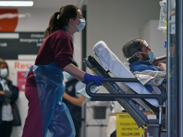 A medical professional in PPE, including gloves, an apron and a face mask as a precautionary measure against Covid-19, pushes a patient, also wearing a facemask, as he lays on a bed, inside St Thomas' Hospital in north London, on April 1, 2020, as life in Britain continues during the …