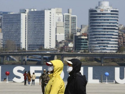 People wearing face masks to help protect against the spread of the new coronavirus walk at a park in Seoul, South Korea, Wednesday, April 8, 2020. The new coronavirus causes mild or moderate symptoms for most people, but for some, especially older adults and people with existing health problems, it …