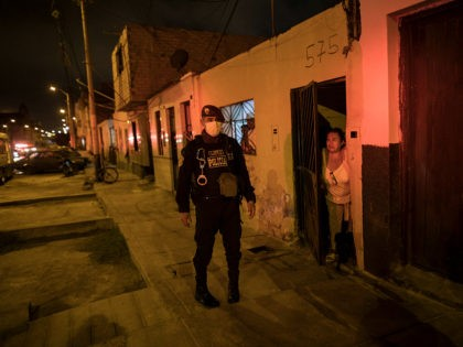 In this April 8, 2020 photo, a neighbor watches a police operation to ensure the curfew declared by the government due to the new coronavirus pandemic, in El Callao, on the outskirts of Lima, Peru. Business has fallen for funeral homes that specialize in selling coffins for victims of violent …