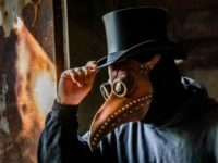 A cosplay of a black plague doctor in a top hat.