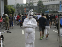 """A man dressed as a shrouded ghost locally known as a """"pocong"""" busks for small money during a car free day in the main business district in Jakarta, Indonesia, Sunday, July 17, 2016. (AP Photo/Dita Alangkara)"""