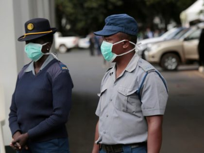 Zimbabwean police wear face masks during a coronavirus awareness campaign launch at State House in Harare, Thursday, March, 19, 2020. For most people, the new coronavirus causes only mild or moderate symptoms. For some it can cause more severe illness, especially in older adults and people with existing health problems. …