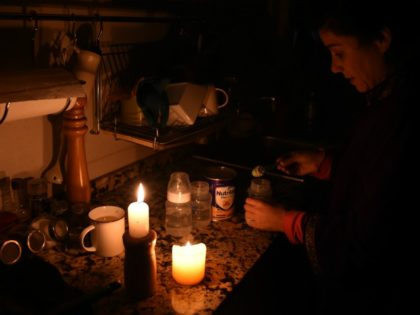 TOPSHOT - A woman prepares milk bottles using candles at her home in Montevideo on June 16, 2019 during a power cut. - A massive outage blacked out Argentina and Uruguay Sunday, leaving both South American countries without electricity, power companies said. (Photo by MIGUEL ROJO / AFP) (Photo credit …