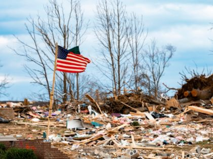 A flag flaps in the wind as US President Donald Trump tours tornado damage in Cookeville, Tennessee on March 6, 2020. - At least 24 are dead in the wake of March 3 2020 terrible Tennessee tornadoes. They carved a long scar across Middle Tennessee in the dead of night, …