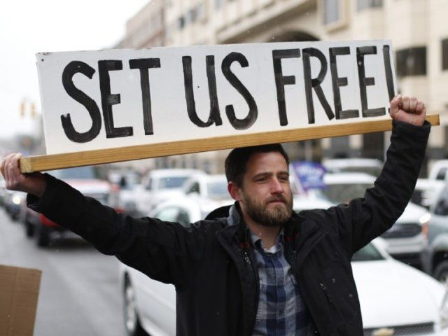 In this April 15, 2020, photo, Steve Polet holds a sign during a protest at the State Capitol in Lansing, Mich. (AP Photo/Paul Sancya)