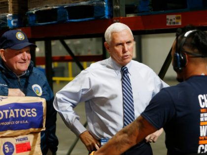 Vice President Mike Pence, center, talks with order picker Bin Sam, right, as Agriculture Secretary Sonny Perdue, left, listens during a tour of a Walmart Distribution Center Wednesday, April 1, 2020, in Gordonsville, Va. (AP Photo/Steve Helber)